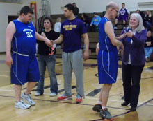 Football receiver Tyler White and Sharon Frandsen, the wife of Albion's interim president, congratulate some of the Special Olympians.