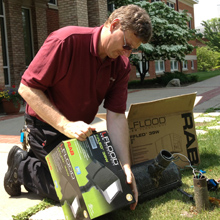 Electrician Brian DeKonnick installs energy-saving LED lights on the quad.