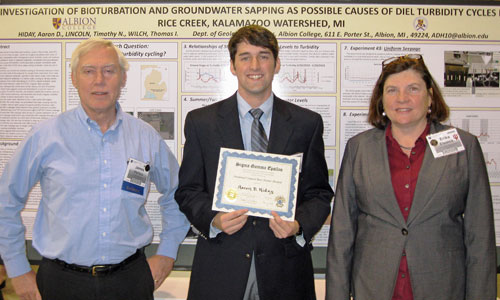 Aaron Hiday, '13, (center) receives his award from Sigma Gamma Epsilon President Erika Elswick and Secretary/Treasurer James C. Walters. Hiday's poster is in the background.
