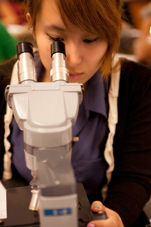 An Albion College student peers into a microscope in a campus science lab.