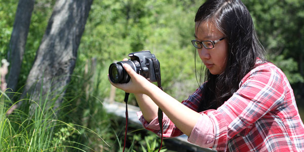 Albion College student Bian Wang shoots photos and video in the Whitehouse Nature Center for her 2012 FURSCA project.