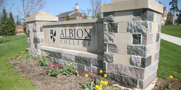 Albion College sign on the southeastern part of campus, with Ferguson Hall (left) and the Kellogg Center in the background.