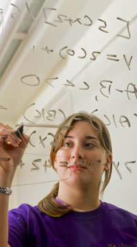 Student writing on a see-through mark-up board.