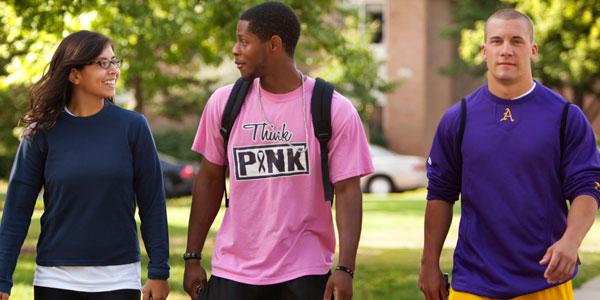 Three Albion College students walking on the Quad.