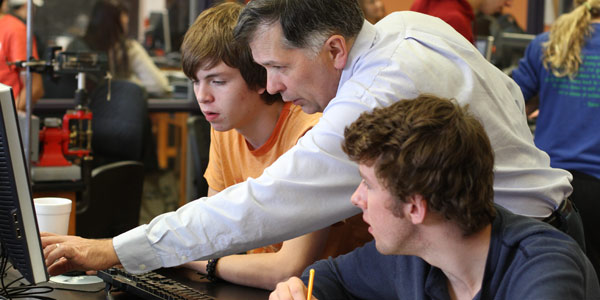 Professor David Seely works with students in a physics lab.