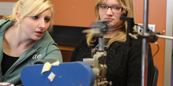 Albion College students conduct an exercise in a physics lab.