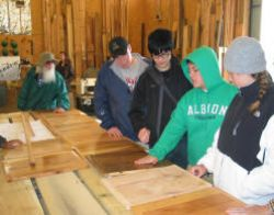 "Students inspecting the forest products at Appalachian Sustainable Development's mill. One effort is to market as ""character wood"" material that otherwise would be considered waste."