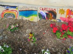Tiles created by children in the complex adorn the base of a demonstration straw bale pavilion in the complex