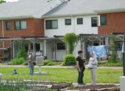 Students stroll amid the gardens of Eco-village residents