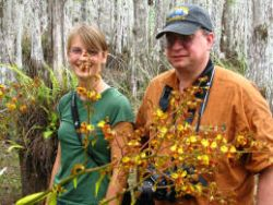 "Alumna Hillary Burgess is presently working on an Everglades restoration project.  She led us on a ""swamp slough' to a cypress dome.  Left, Hillary shows her mentor, Biologist Dan Skean some orchids in bloom.  Right, John poses with ferns in the dome"