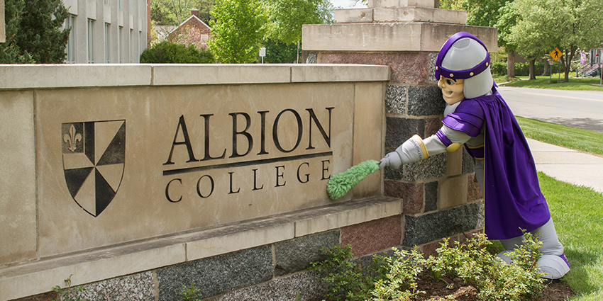 Brit Briton cleaing the Albion College sign.