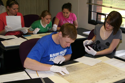 Albion College history students handling and studying original documents.