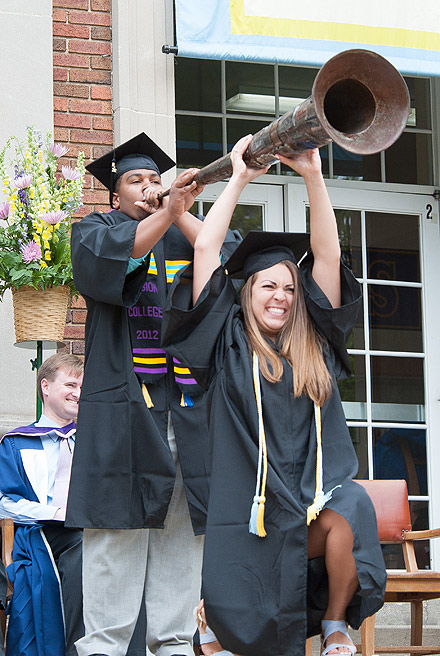 Jordan Raiford, assisted by Sam Salhaney, sounds the Senior Horn at Commencement 2012.