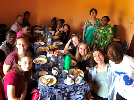 French students in Cameroon eating together at a table.