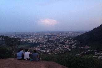 Students sit on the top of a hill overlooking the town.