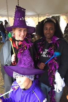 Student's in purple witch hats, holding wands.