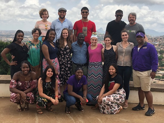 French students in Cameroon posing with the city behind them.