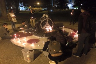 A candlelight vigil at Albion's rock. The rock is painted black with a silver Eiffel tower/peace sign.