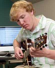 An Albion music student works in the Goodrich lab with his guitar.