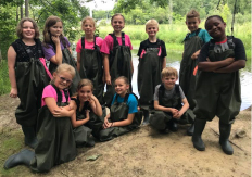 Kids in waders, by the Kalamazoo river during one of Whitehouse Nature Center's Summer Camps.