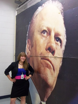 Colleen Ouendag, '12, stands next to a billboard of Gerald R. Ford kept in collections at the Ford Presidential Museum in Grand Rapids.