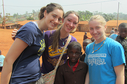 Melissa Woodard, Kim Hagel, and Alyssa Heilman with a girl they met at one of the schools the Albion group visited.