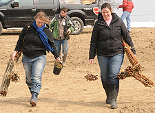 Heather Norbert, '12, left, and Property Manager Charlsie Sederlund carry plugs of small trees to grow in the wetland.