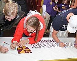 Students sign a thank-you banner