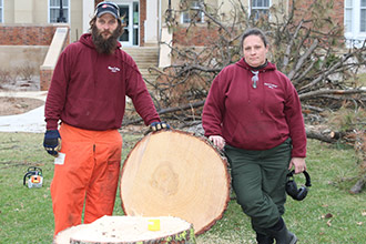Brother and sister Joey Reynolds and Mary Nash, part of the Albion College grounds staff, stand alongside the tree originally planted by their grandfather, John Reynolds, '39, when he was an Albion College student.