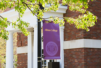 An Albion College lamp post banner outside Robinson Hall.