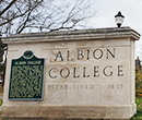 Albion College sign with State of Michigan historical marker at the Michigan Avenue entrance to campus.