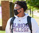 An Albion College student walks through the athletic complex.