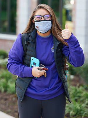An Albion College student gives the thumbs-up sign on the Quad, fall 2020.