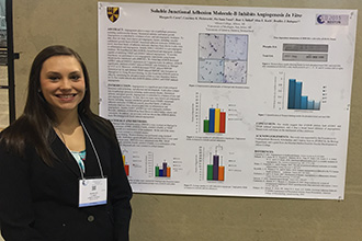 Morgan Carey stands next to her research poster at the 2015 Experimental Biology conference in Boston.