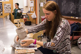 "Emily Allison, '18, works with her Toby Jug in her ""Ceramics in the Industrial Revolution"" Honors class. Professor Lynne Chytilo speaks to the class in the background."