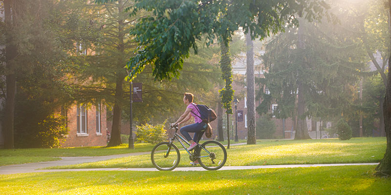 Dr. Jess Roberts, professor of English, pedals on the Albion College Quad.