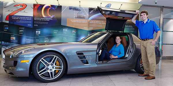 Ross Muniga, '15 (standing), Brooke Kaltz, '05 (seated), and a Mercedes-Benz sports car.