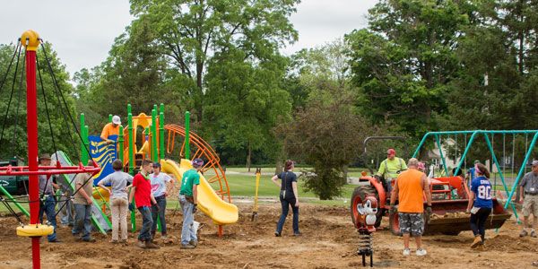 Albion community members and the College's Build Albion Fellows work with members of Naperville, Illinois, Knox Presbyterian Church youth group on Albion's Holland Park playground