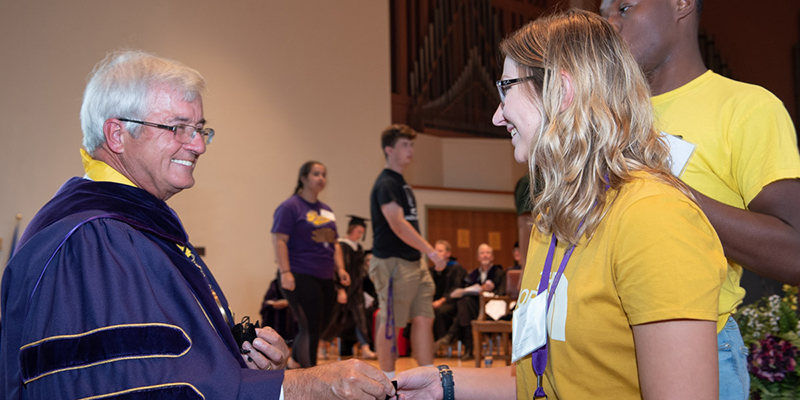 Albion College 2018 Matriculation, receiving coins