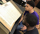 Nathan Kellum, '19 (top), and Shane Mills, '19 look at pages of The Liberator, a 19th-century abolitionist newspaper, at a library in Philadelphia, summer 2018.