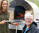 Albion College women's and gender studies professor Trisha Franzen and a student in front of the pizza oven Franzen's first-year seminar class built.