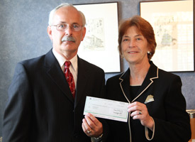 State Farm agent Mark Putvin presents the $20,000 grant check to Albion College President Donna Randall.