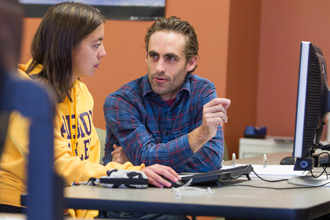 An Albion College student works with a faculty member at a computer station.