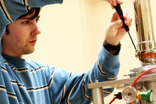 An Albion College physics student adjusts equipment in the lab.